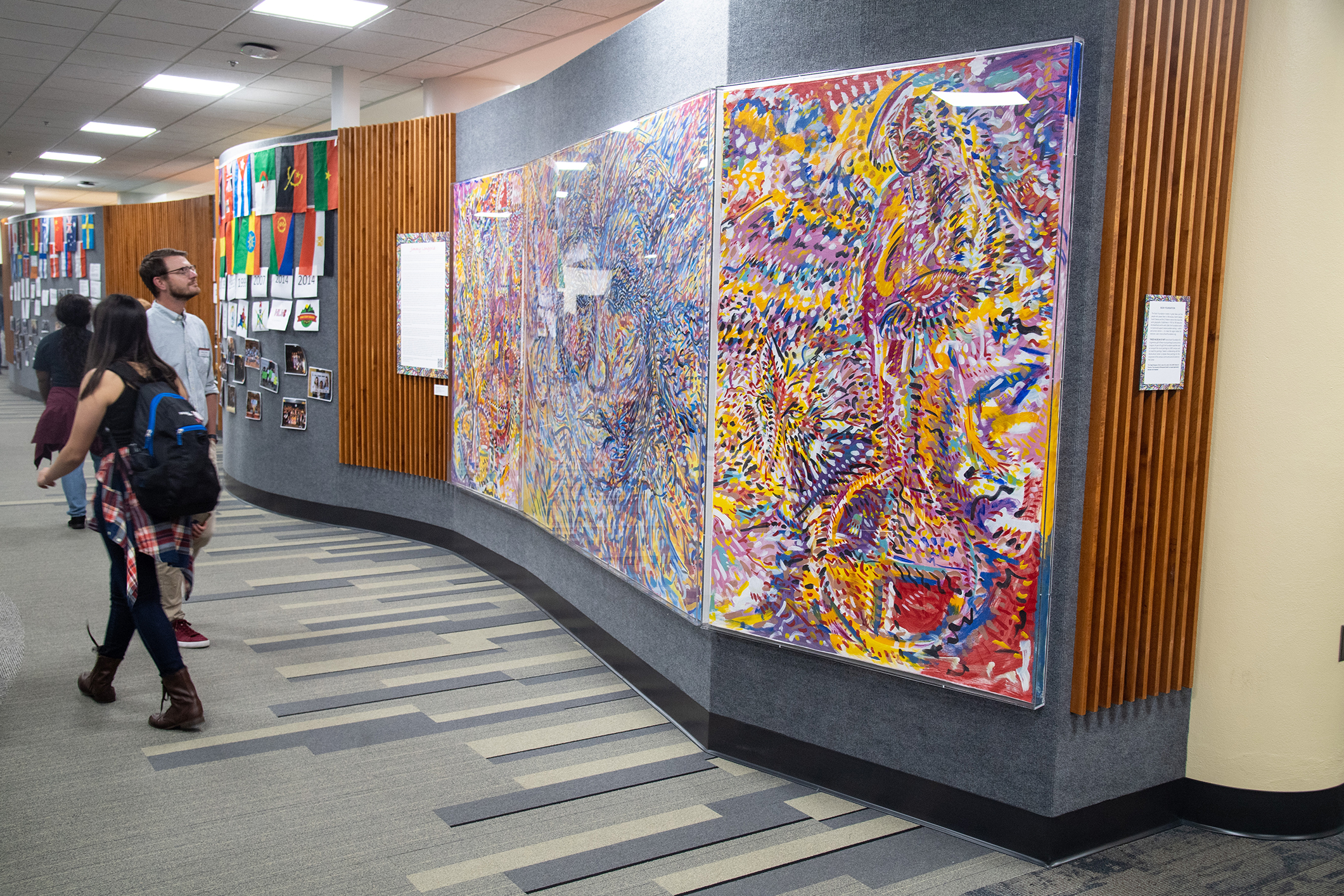 Students walking through the Multicultural Center past colorful painting