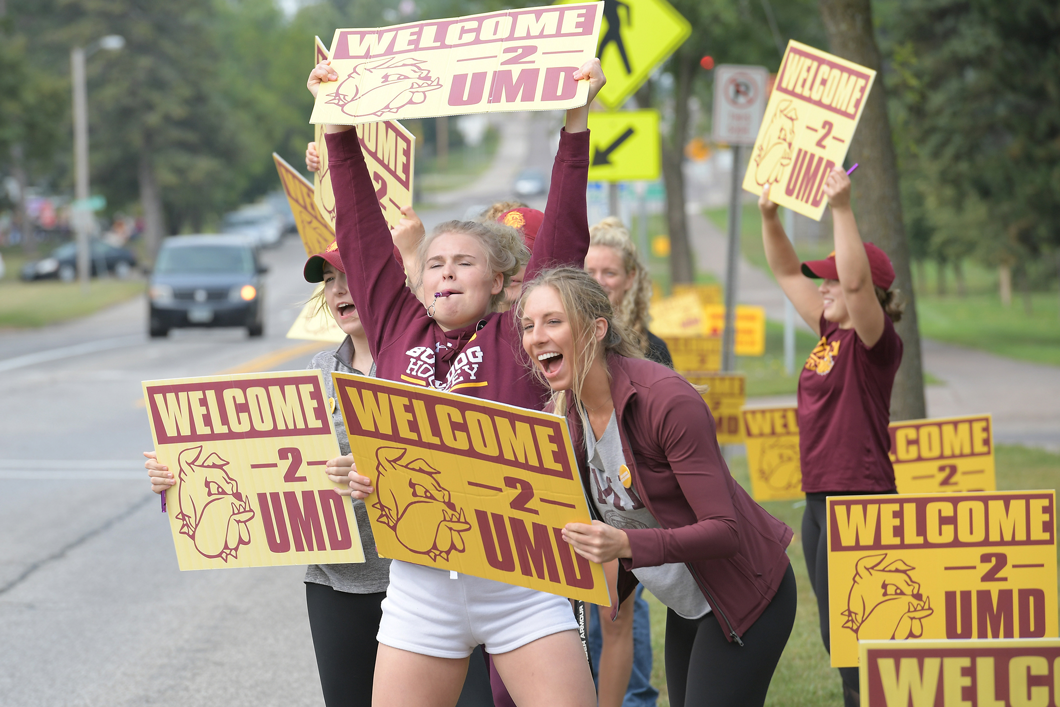 Students welcoming incoming students with signs